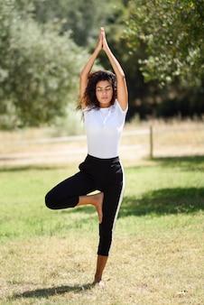 Giovane donna araba che fa yoga in natura