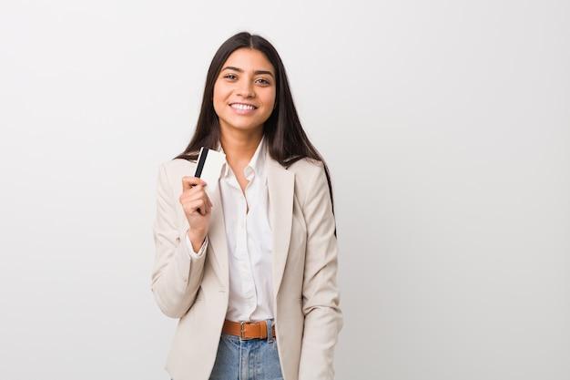 Giovane donna araba che giudica una carta di credito felice, sorridente e allegra.