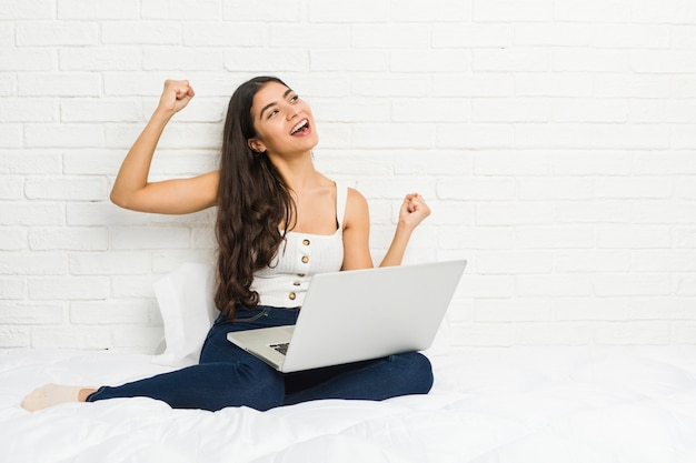 Giovane donna araba che lavora con il suo computer portatile sul letto che alza pugno dopo una vittoria, concetto del vincitore.