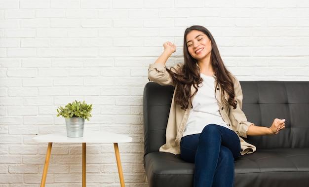 Giovane donna araba che si siede sul divano ballare e divertirsi.