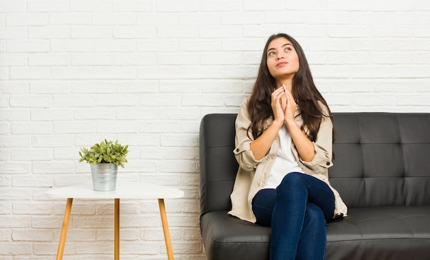 Giovane donna araba che si siede sul divano inventando il piano in mente, creando un'idea.