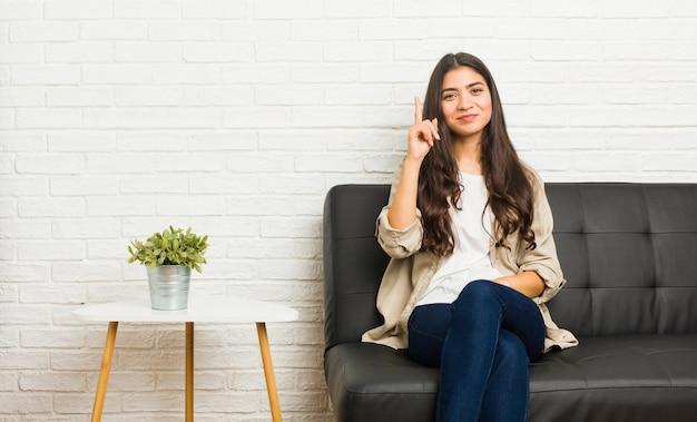 Giovane donna araba che si siede sul sofà che mostra numero uno con la barretta.