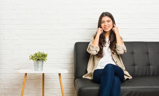 Giovane donna araba che si siede sulle orecchie della copertura del sofà con le mani.