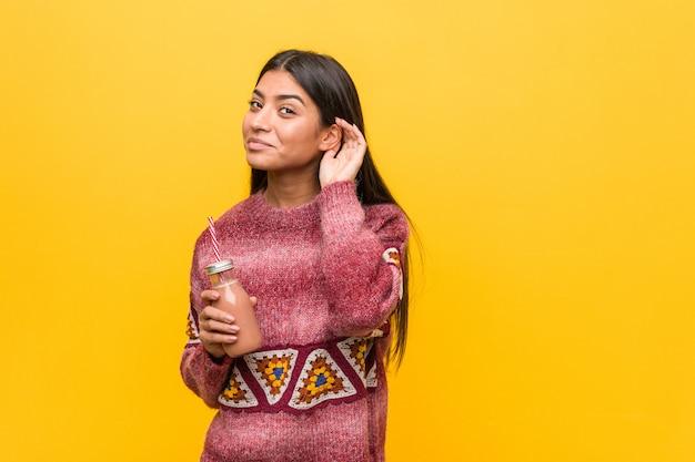 Giovane donna araba che tiene un frullato che prova ad ascoltare un gossip.