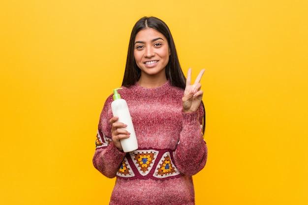 Giovane donna araba che tiene una bottiglia crema che mostra numero due con le dita.