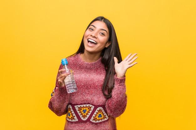 Giovane donna araba che tiene una bottiglia d'acqua per celebrare una vittoria o un successo