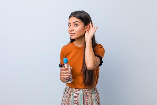 Giovane donna araba che tiene una bottiglia di acqua che prova ad ascoltare un gossip.