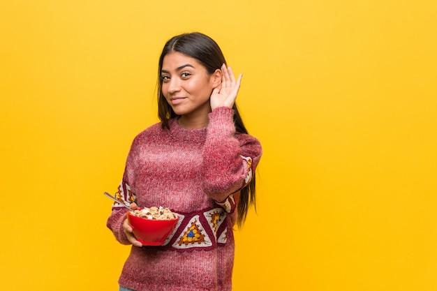 Giovane donna araba che tiene una ciotola di cereali cercando di ascoltare un gossip.