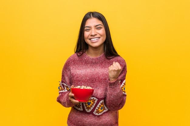 Giovane donna araba che tiene una ciotola di cereali incoraggiante spensierata ed eccitata. concetto di vittoria.