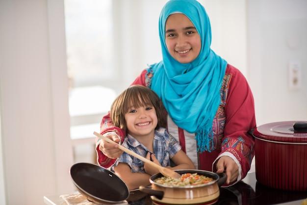 Giovane donna araba con il ragazzino in cucina