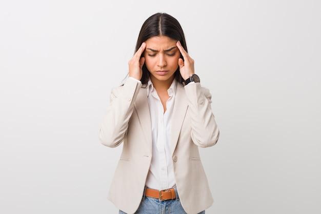 Giovane donna araba di affari isolata contro un fondo bianco che tocca le tempie e che ha mal di testa.