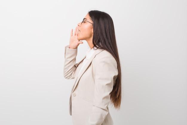 Giovane donna araba di affari isolata su bianco che grida e che tiene il palmo vicino alla bocca aperta.