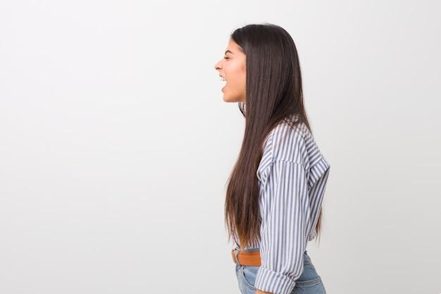 Giovane donna araba graziosa che grida verso uno spazio della copia