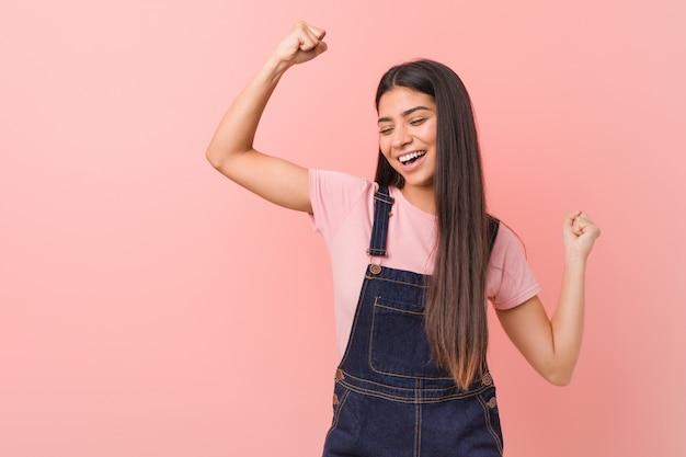 Giovane donna araba graziosa che indossa un denim dei jeans che alza pugno dopo una vittoria, concetto del vincitore.