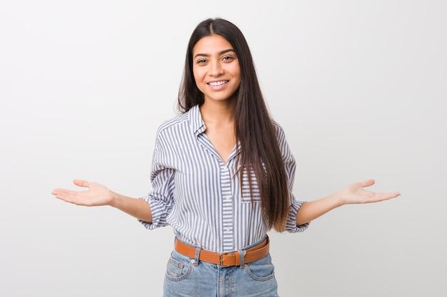 Giovane donna araba graziosa che mostra un'espressione benvenuta.
