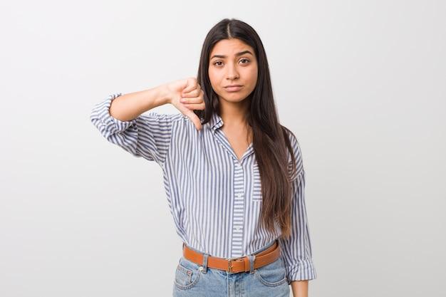 Giovane donna araba graziosa che mostra un gesto di antipatia, pollici giù. disaccordo .