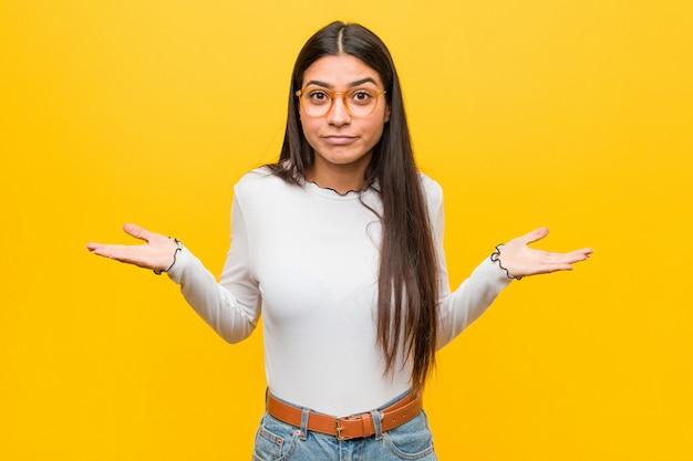 Giovane donna araba graziosa contro il giallo che dubita e che scrolla le spalle le spalle nel gesto interrogante.