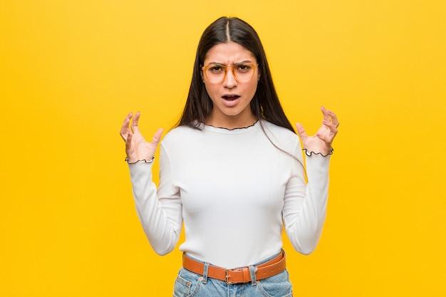 Giovane donna araba graziosa contro il giallo che grida con rabbia.