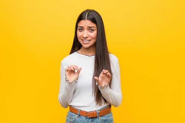 Giovane donna araba graziosa contro il giallo che rifiuta qualcuno che mostra un gesto di disgusto.