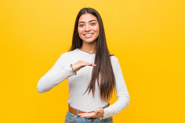 Giovane donna araba graziosa contro una priorità bassa gialla che tiene qualcosa con entrambe le mani, presentazione del prodotto.