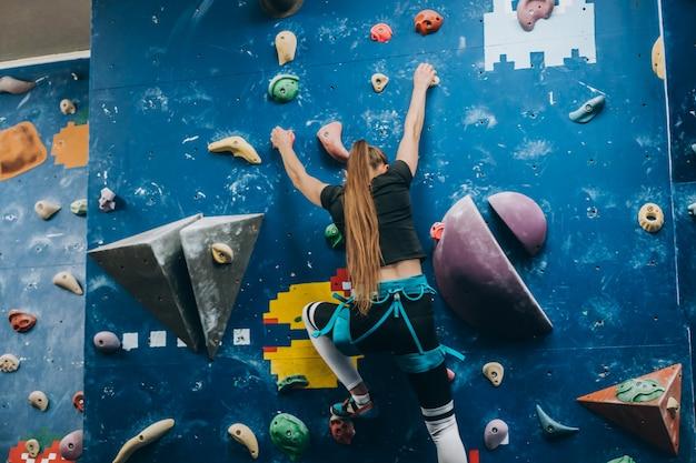 Giovane donna arrampicata su una parete di arrampicata su roccia alta, coperta, artificiale