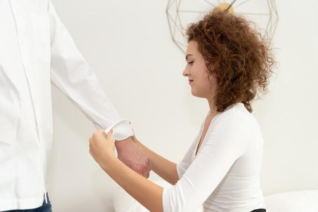 Giovane donna arrotolando le maniche del suo fidanzato