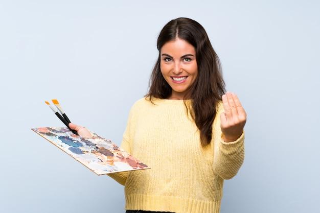 Giovane donna artista su muro blu isolato che invita a venire con la mano, felice che tu sia venuto