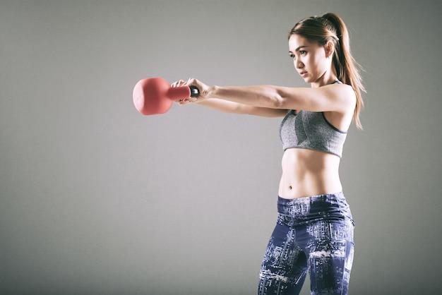 Giovane donna asiatica adatta che si esercita con kettlebell
