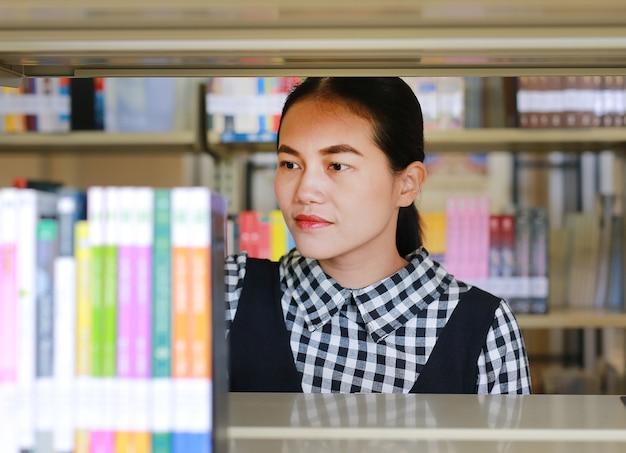 Giovane donna asiatica alla ricerca sullo scaffale per libri in biblioteca.