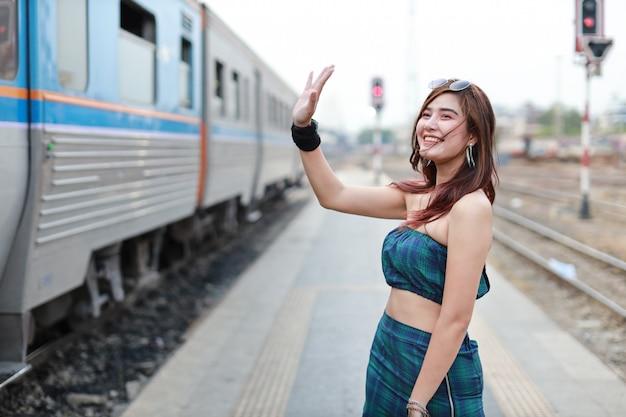 Giovane donna asiatica alzando la mano a qualcuno nella stazione ferroviaria con la faccia sorridente