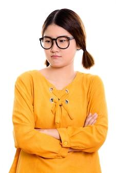 Giovane donna asiatica arrabbiata guardando in basso con le braccia incrociate