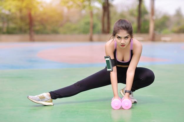 Giovane donna asiatica atletica che allunga e che solleva le teste di legno