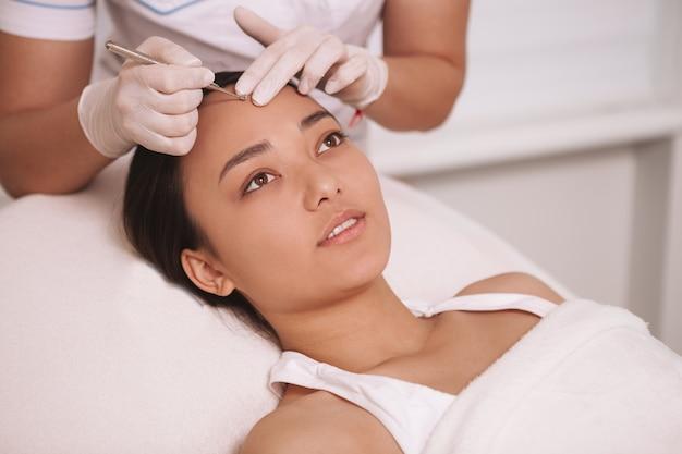 Giovane donna asiatica attraente che ha procedura di rimozione del comedone al salone di cosmetologia