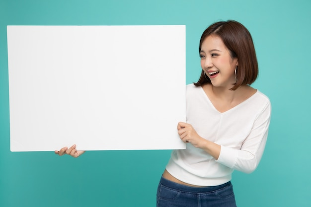 Giovane donna asiatica attraente che mostra e che tiene cartello bianco in bianco