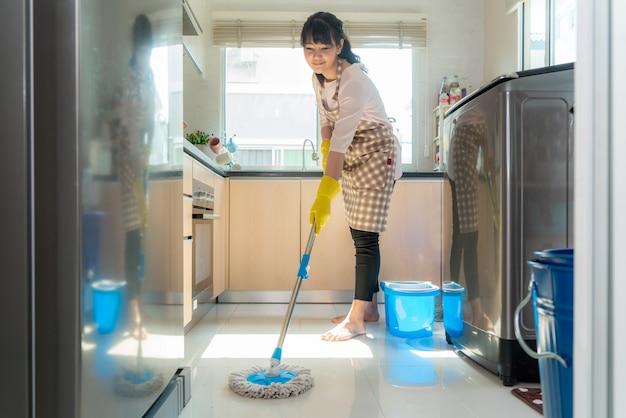 Giovane donna asiatica attraente che passa lo straccio sul pavimento della cucina alla cucina mentre facendo pulizia a casa durante il soggiorno a casa usando il tempo libero circa la loro routine quotidiana di governo della casa.