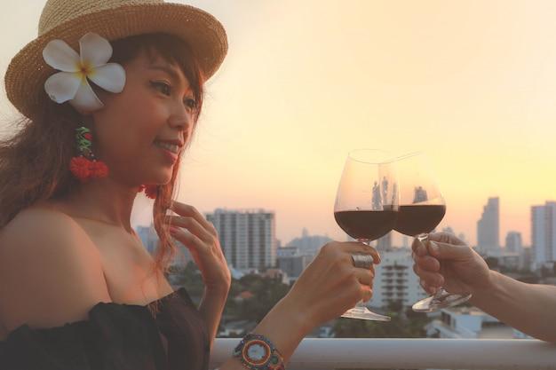 Giovane donna asiatica attraente che tosta il vetro del vino rosso sul terrazzo, stile d'annata