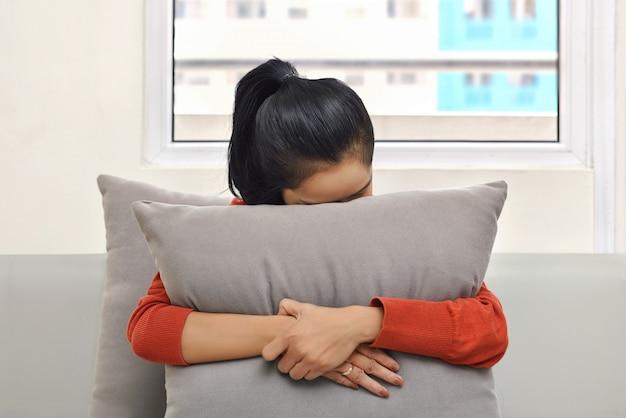 Giovane donna asiatica che abbraccia e che si nasconde dietro un cuscino