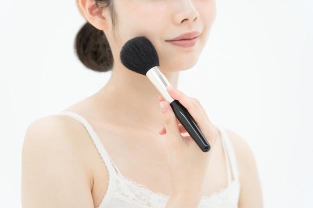 Giovane donna asiatica che applica trucco con una spazzola molle