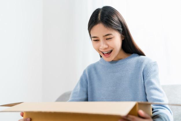 Giovane donna asiatica che apre una scatola mentre sedendosi sul sofà