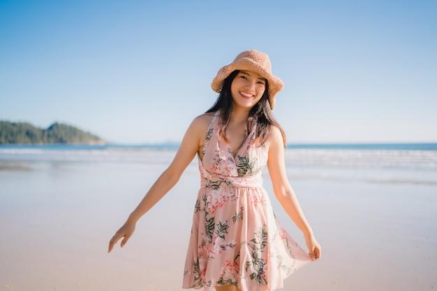 Giovane donna asiatica che cammina sulla spiaggia. la bella femmina felice si distende camminando sulla spiaggia
