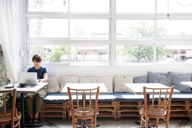 Giovane donna asiatica che cerca informazioni di viaggio tramite computer portatile mentre sedendosi nel caffè.
