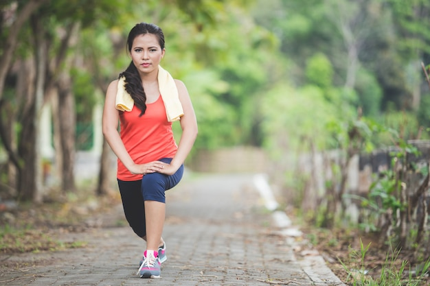 Giovane donna asiatica che fa esercizio all'aperto in un parco, allungante