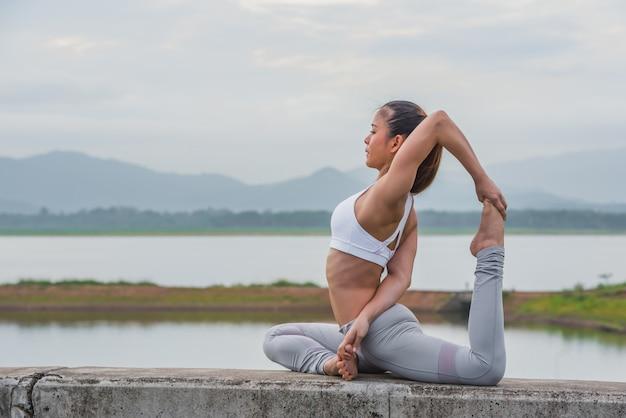 Giovane donna asiatica che fa yoga sulla sponda del fiume.