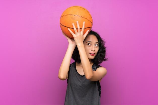 Giovane donna asiatica che gioca a basket