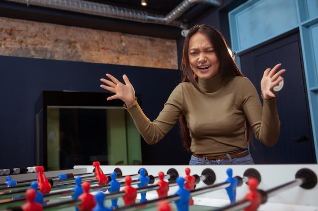 Giovane donna asiatica che gioca calcio balilla