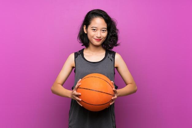 Giovane donna asiatica che gioca pallacanestro sopra la parete viola isolata