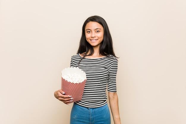 Giovane donna asiatica che giudica un secchio del popcorn felice, sorridente e allegro