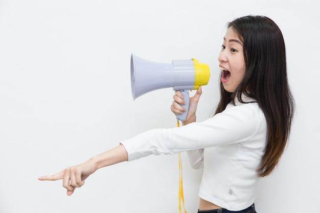 Giovane donna asiatica che grida e che grida con il megafono su fondo bianco