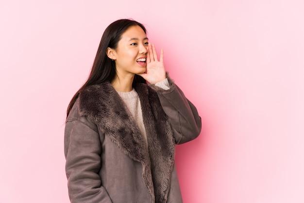 Giovane donna asiatica che indossa un cappotto che grida e che tiene la bocca aperta vicina della palma