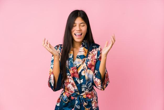 Giovane donna asiatica che indossa un pigiama del kimono che ride molto. concetto di felicità.